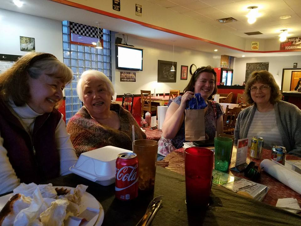 The April book club meeting garnered Bethany Mead her second game prize winning in as many months.  From left to right, Karen Levine, Louise Janelle, Mead, and Pamela Recko enjoy the food, companionship, and discussion.