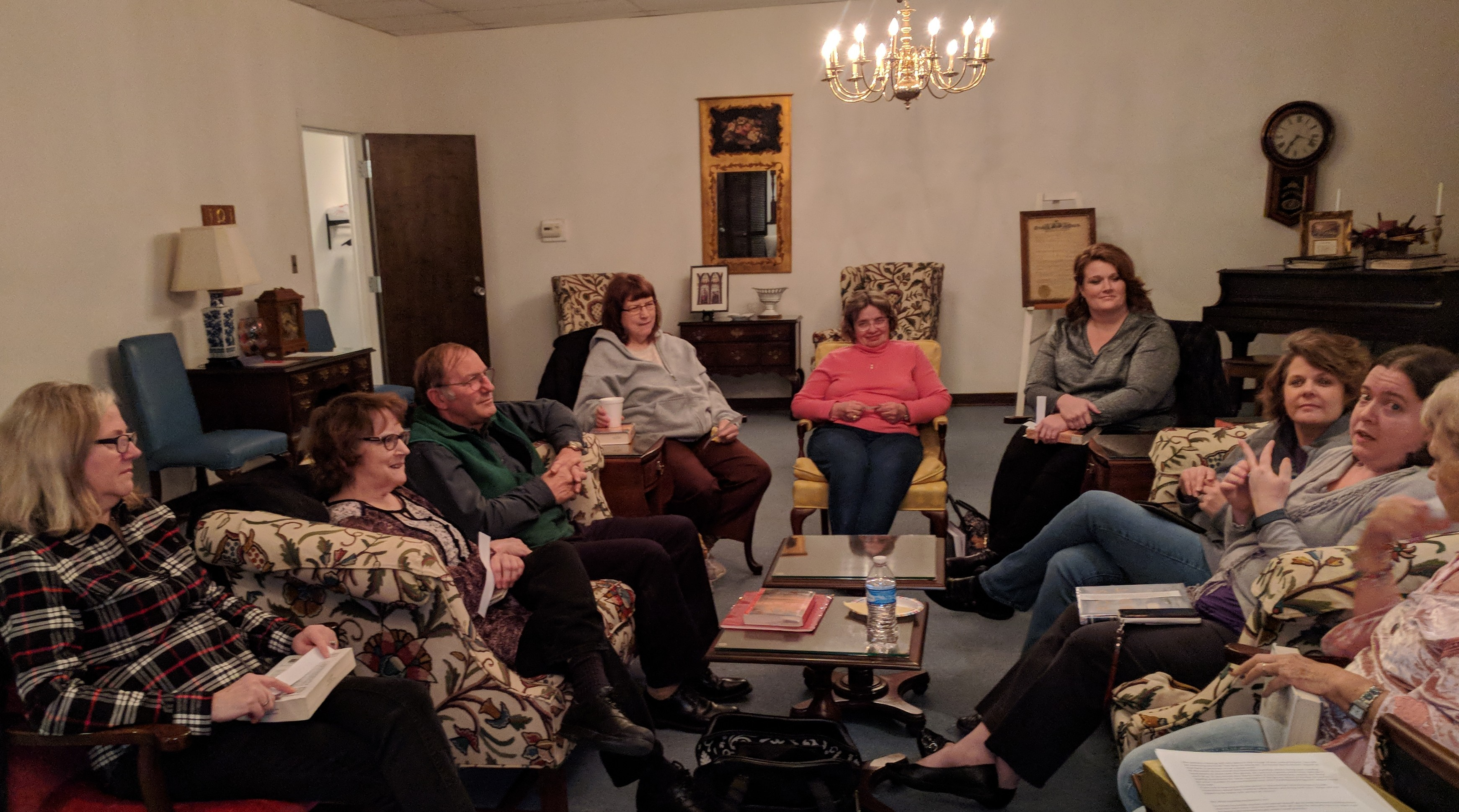 9 of the 12 people in attendance at the first book club meeting of the new year are seen here while discussing the book of the month.