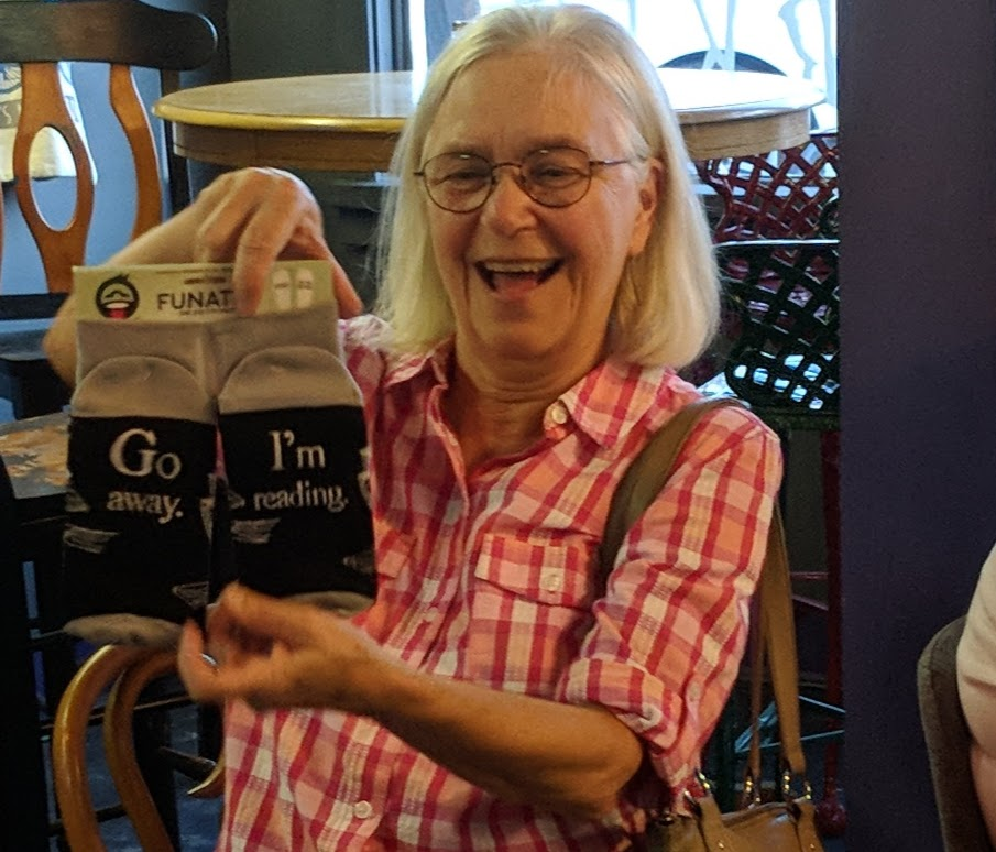 After playing a fun game at the June book club meeting, Carolyn Tadlock won the prizes donated for June by fellow book clubber, Bethany Mead.  She received a box full of items.