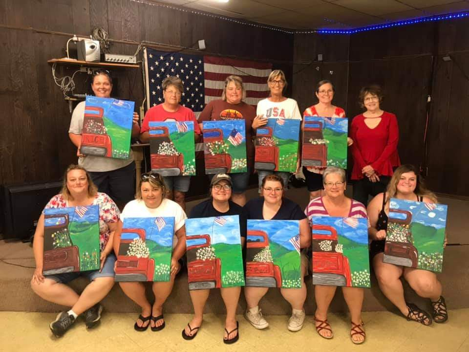 Some of those in attendance are seen here with their paintings from the Friends of the Library's Patriotic Summertime Sip & Paint event.