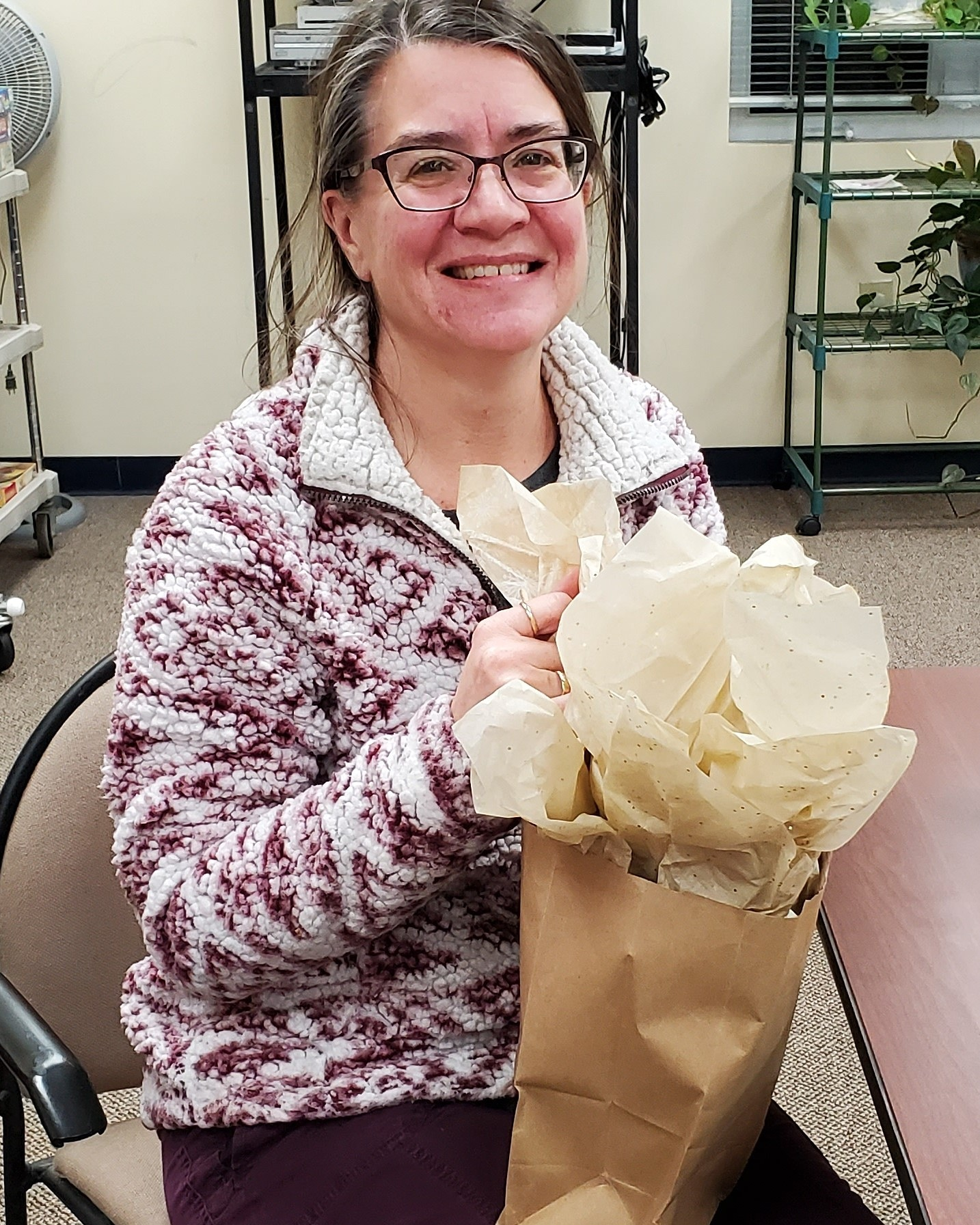 "Newest member Deanna won the prize drawing at January's ""Around Town' Book Club meeting. She won a soup mug, honey soaps, and a book bag."