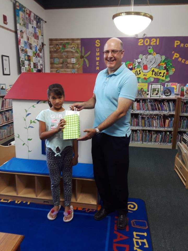 Esmeralda Rodriguez won a $50 Walmart giftcard for Summer Reading presented by library director Steve Brindza.