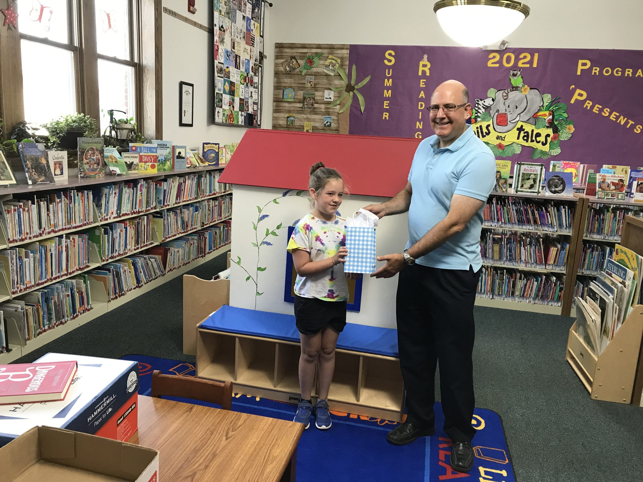 Emily Hignite was a top winner in the Mt. Sterling Public Library's Tails & Tales Summer Reading Program's reading challenge. Library director Steve Brindza is seen here presenting her with a $50 Amazon gift card.